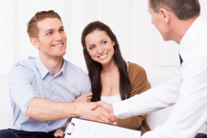 Sealing a deal. Happy young man shaking hand to financial agent while sitting together with his wife